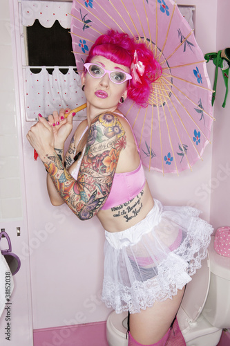 Tattooed woman in eyeglasses holding parasol