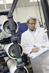 Man writing in clipboard while standing in bottling factory