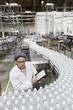 High angle view of man examining bottles at bottling plant