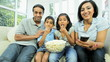 Young Asian family Watching TV with Popcorn