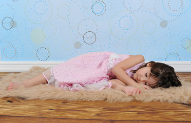 sweet little girl asleep on furry brown rug