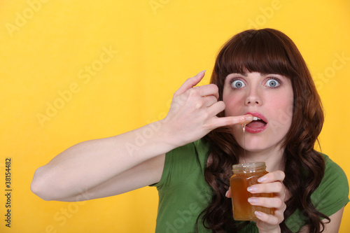 Woman dipping finger in honey jar