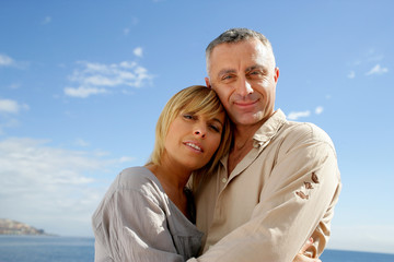 Couple hugging against a blue sky