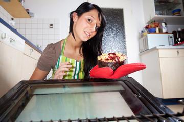 Frau holt einen Kuchen aus Backofen