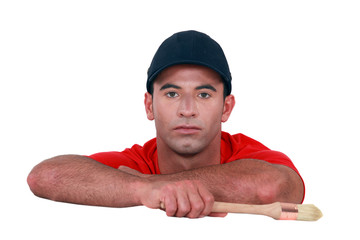 Bored man holding a paintbrush