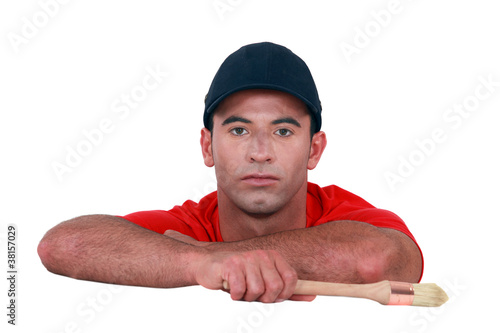 Bored man holding a paintbrush
