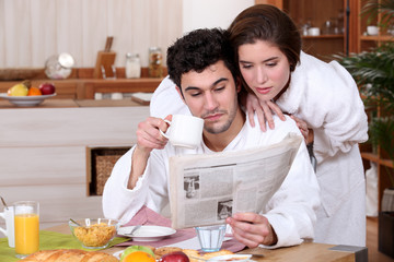 Young couple reading a newspaper at breakfast