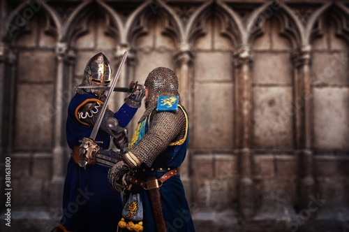 Two knights fighting agaist medieval cathedral wall.