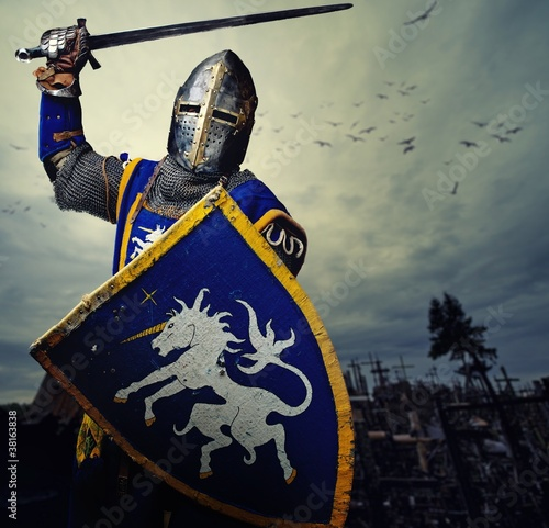 Medieval knight against hill full of crosses. - 38163838