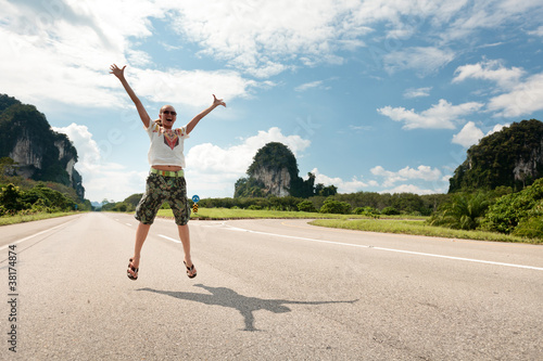 Pretty young woman hitchhiking along a road in tropical location
