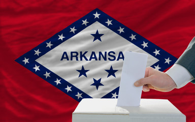man voting on elections in front of flag US state flag of arkans