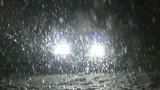 Snow falls on the road in the headlights