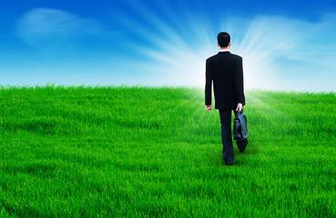 Businessman walks heading to the sun