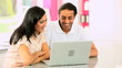 Young Ethnic Couple Online with Wireless Laptop