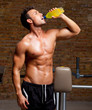 muscle man at gym relaxed with energy drink