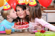 sisters kissing mom at birthday's party