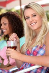 Two female friends having drink on terrace