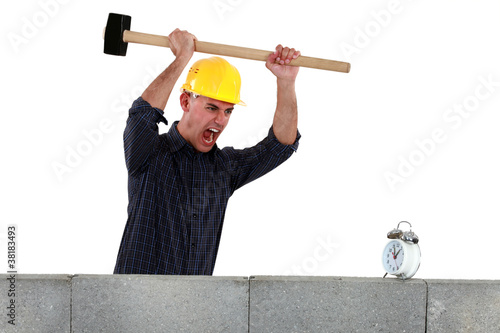 Tradesman about to smash an alarm clock
