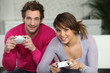 Young couple playing a games console