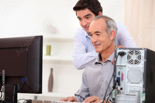 Young man teaching an elderly man computer skills