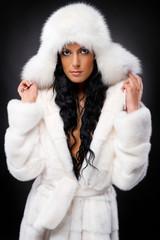 Beautiful woman in white fur coat and cap