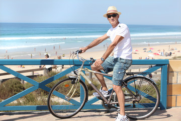 man with a bike at the beach