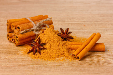 Cinnamon sticks, powder and anise on wooden table