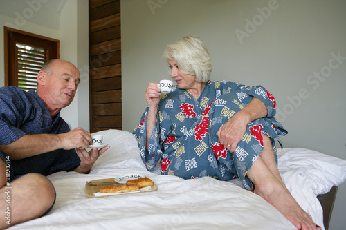 Senior couple in bathrobe sitting on a bed having breakfast