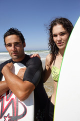 Young surfer couple stood on the beach with their surfboards