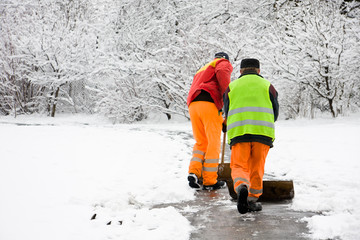 Unidentified workers removing first snow from pavement