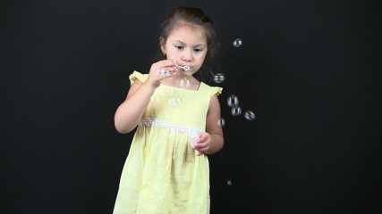 child blowing bubbles in studio
