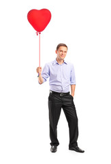 Smiling young man holding a red heart shaped balloon