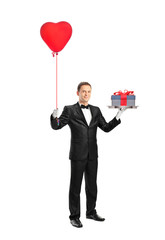 Waiter holding a red heart shaped balloon and a gift