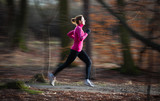 Fototapety young woman running outdoors in a city park on a cold fall