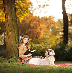 Smiling young woman relaxing in a city park with her dog