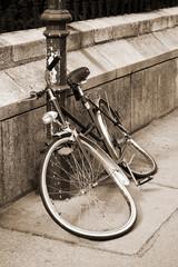 Abandoned damaged bicycle locked to an iron pillar on sidewalk