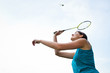 Pretty, young woman playing badminton in a city park