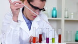 Scientist using pipette to add substance to test tubes
