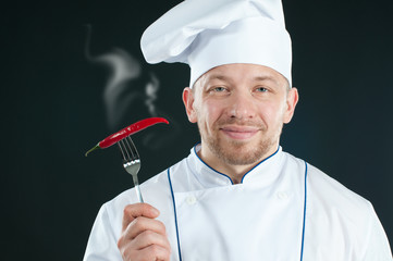 Smiling chef holding a fork with hot chili pepper