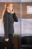 Businesswoman on phone arriving to office