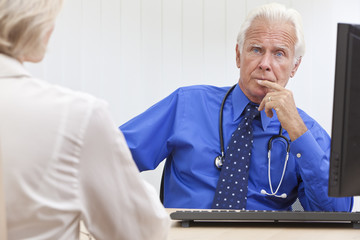 Thoughtful Senior Male Doctor With Computer