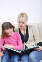Mother and daughter sitting in living room reading book