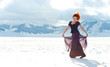 Portrait of beautiful red woman dancing in the snow in winter