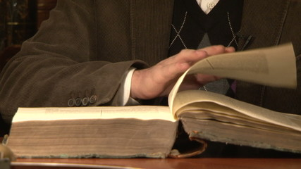 The man flips through an old book
