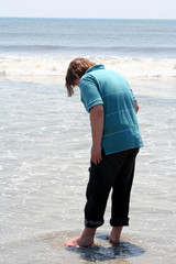 Teen Boy Stepping Into Ocean Surf