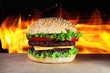 big hamburger with real fire on a background