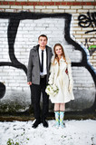 Happy bride and groom against a wall with graffiti