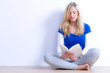 junge frau sitzt entspannt auf dem boden und liest ein buch