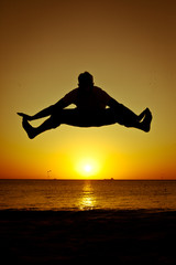 Silhouette of a man jumping on the beach at sunset