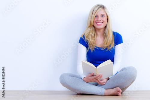 hübsche studentin sitzt mit einem buch auf dem boden